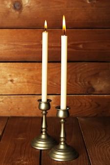 Ретро подсвечники со свечами на деревянных фоне