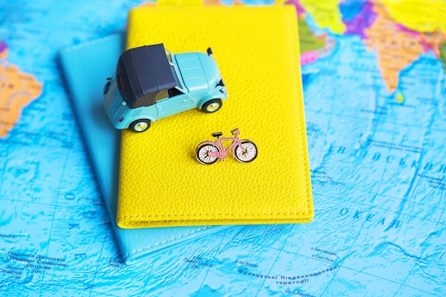 Retro car and bicycle on colorful world map, passport
