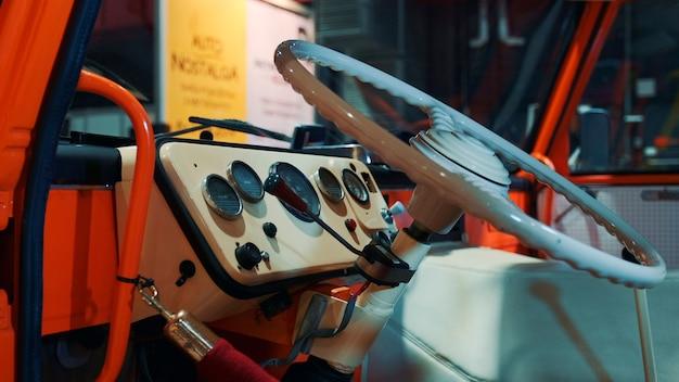 ミルクカラーのクラシックなヴィンテージインテリアのレトロな車のダッシュボードとステアリングホイール