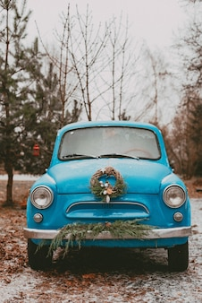Retro car decorated with festive christmas tree branches, gift boxes craft wrapping paper wreath pine fir needles. new year trip. car in the snow forest.