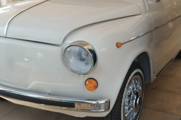 丸いヘッドライトの正面図と白のレトロな車