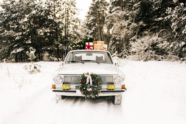 Retro car with gifts and christmas tree