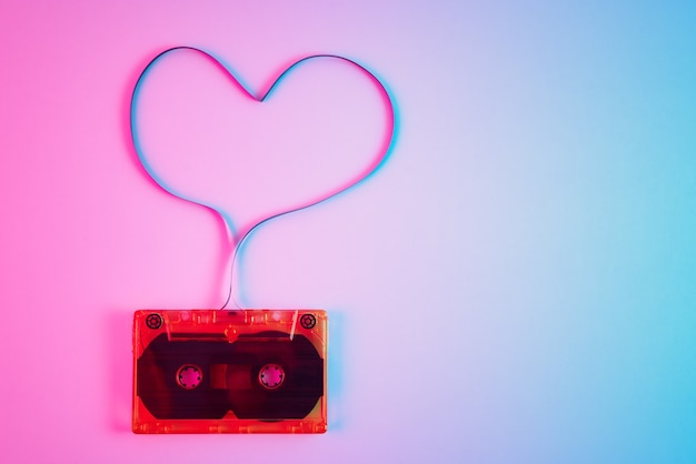 Retro cassette on colorful neon background with magnetic tape in shape of heart