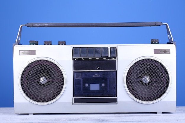 青い表面のテーブルにレトロなカセットステレオレコーダー