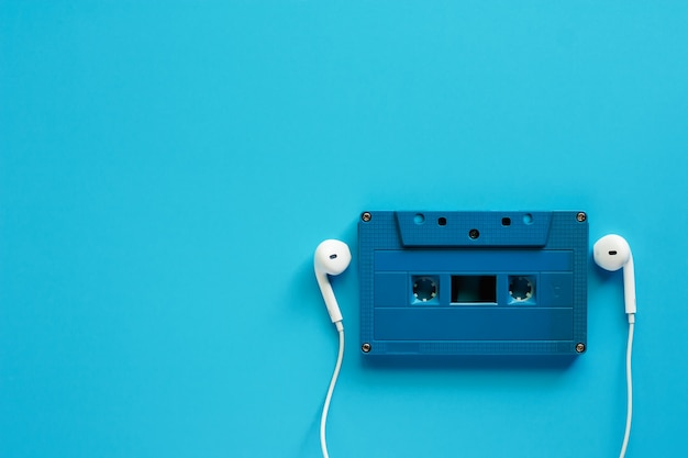 Retro cassette tape with earphones on blue background for music and relaxation concept