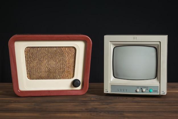 Ретро монитор видеонаблюдения и старинное радио на деревянном столе на черном фоне. набор старинного радиооборудования.