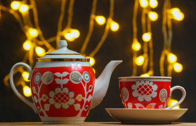 Retro ceramic cup and teapot on dark blurred with light bulbs.