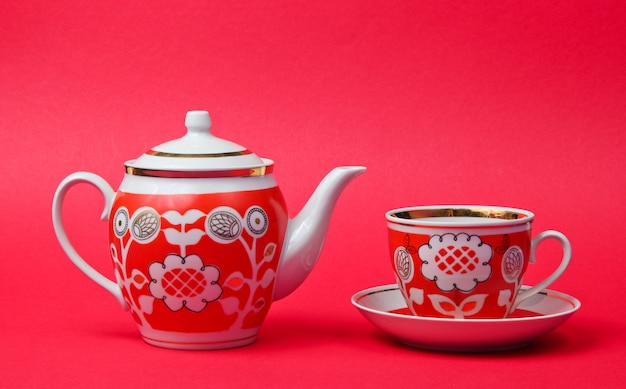 Retro ceramic cups and teapot isolated on red