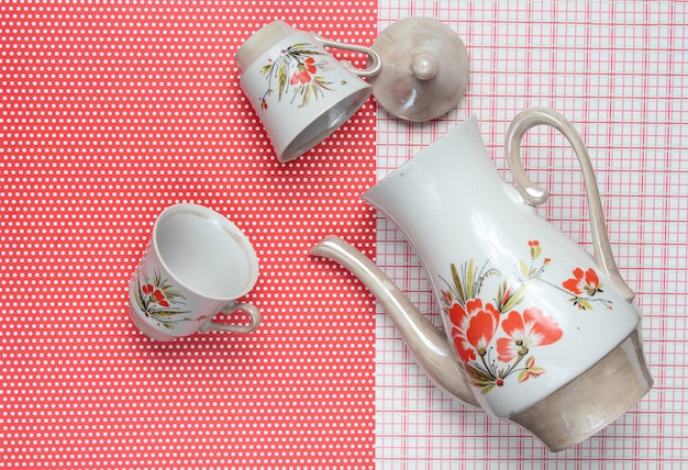 Retro ceramic cups and teapot with red patterns on tablecloth. top view