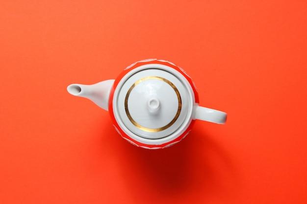 Retro ceramic teapot on orange paper table.