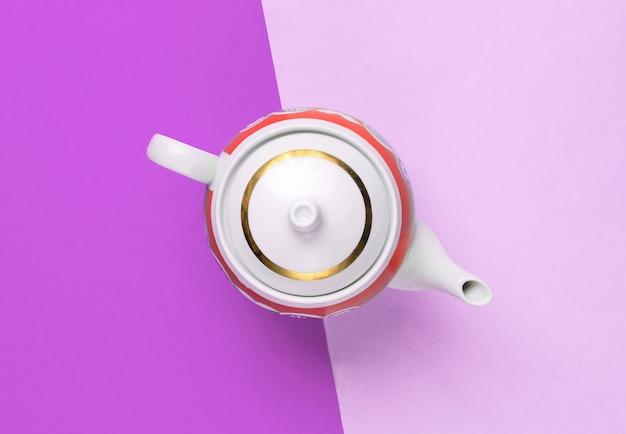 Retro ceramic teapot on purple paper