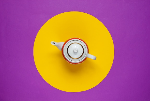 Retro ceramic teapot on a purple with yellow circle in the middle