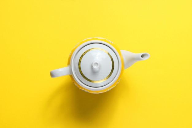 Retro ceramic teapot on yellow paper