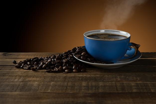 素朴なテーブルの煙から出てくるレトロなコーヒーカップ。