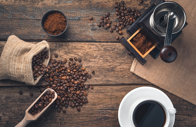 Retro coffee wall with copy space. a cup of coffee, coffee beans and a coffee grinder on a wooden wall. top view.