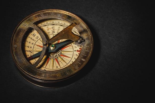 Retro compass on black board background.