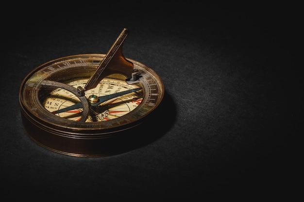 Ретро компас на доске черный стол.