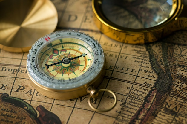 Retro compass with old map and magnifier closeup