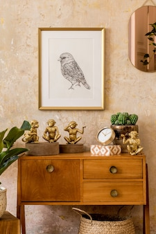 Retro composition of living room interior with wooden vintage commode, gold pink mirror, mock up poster frame, plant, decoration and elegant personal accessories in wabi sabi home decor.