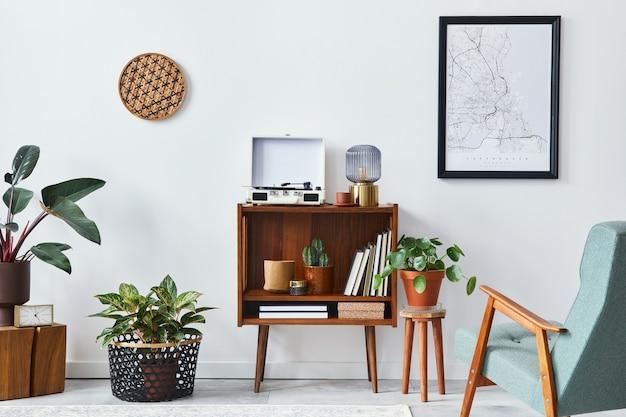 세련된 가정 장식의 모의 포스터 지도, 나무 선반, 책, 안락의자, 식물, 선인장, 비닐 녹음기, 장식 및 개인 액세서리가 있는 거실 인테리어의 복고풍 구성