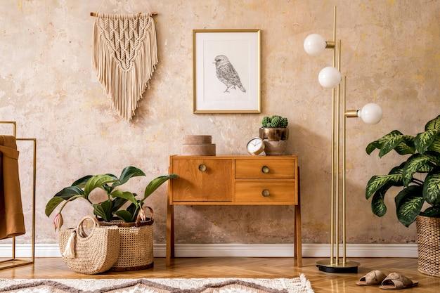 木製のヴィンテージのcommode、灰色のソファ、金のランプ、マクラメ、カーペット、枕、金のモックアップポスターフレーム、植物、装飾、パーソナルアクセサリーを備えたリビングルームのレトロな構成。