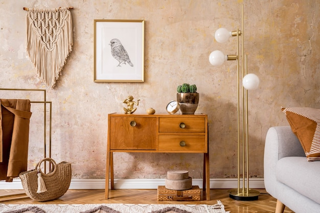Ретро композиция гостиной с деревянным винтажным комодом, серым диваном, золотой лампой, макраме, ковром, подушками, золотой макет рамки плаката, растениями, украшениями и личными аксессуарами.