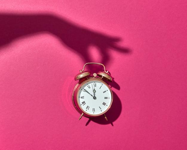 Ретро медный будильник с жесткими тенями от руки женщины на ярко-розовом фоне, копией пространства.