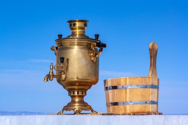 レトロな銅のサモワールと水用の木製の浴槽が青い空を背景に氷皿の上に立っています。ロシアのやかんは薪で動作します。水平。