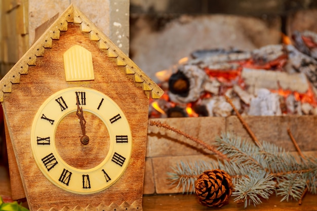 Retro cuckoo clock with roman numerals on the background of a fireplace with fire. on the clock face 12 hours without 5 minutes.