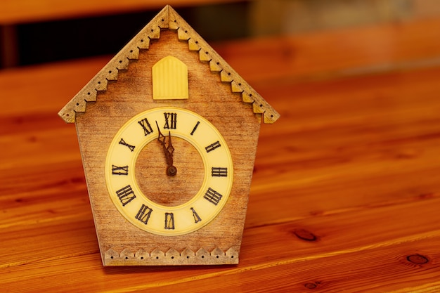 Retro cuckoo clock with roman numerals on a wooden table. on the clock face 12 hours without 5 minutes.