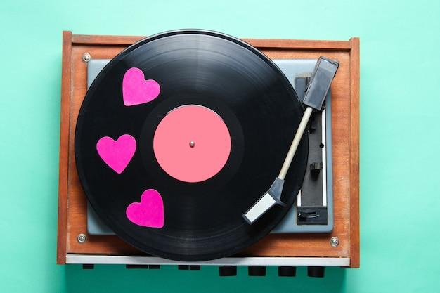 Ретро культура. декоративные сердечки на виниловой пластинке на мятном фоне.