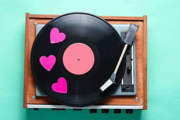 Retro culture. decorative hearts on a vinyl record plate on mint-colored background.