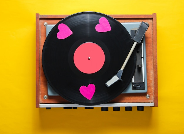 Retro culture. decorative hearts on a vinyl record plate on yellow background.
