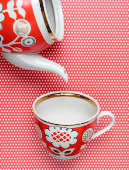 Ретро чашка и чайник с красными узорами на скатерть с горошек. вид сверху