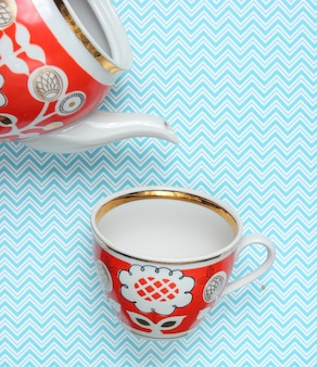 Retro cup and teapot with red patterns on tablecloth. top view