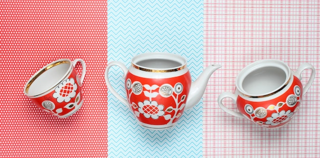 Retro cups and teapot with red patterns on tablecloth. top view