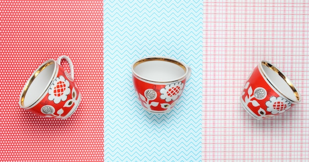 Retro cups with red patterns on tablecloth. top view