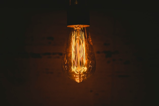 Retro decorative light bulbs lighted of warm color on dark wooden background.