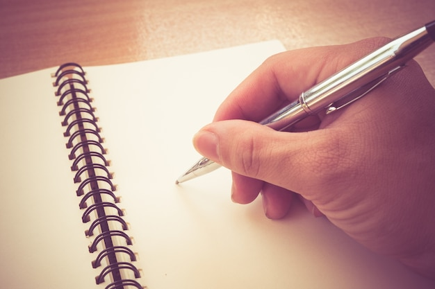 Retro effect faded and toned image of a writing a note with a fountain pen