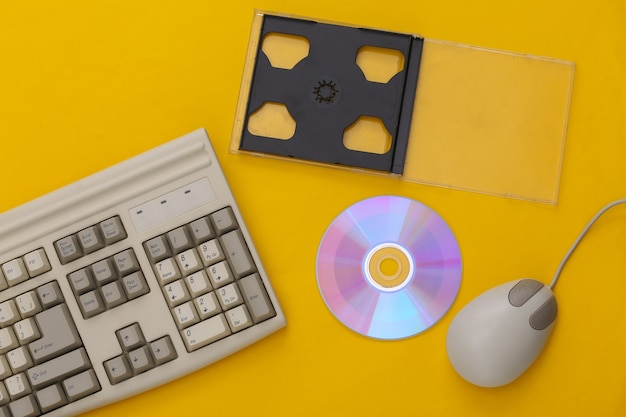Ретро-электроника, компьютерная техника 90-х годов. клавиатура пк, мышь, компакт-диск на синем фоне. вид сверху