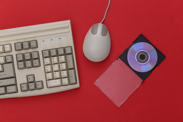 Ретро-электроника, компьютерная техника 90-х годов. клавиатура пк, мышь, компакт-диск на красном фоне. вид сверху