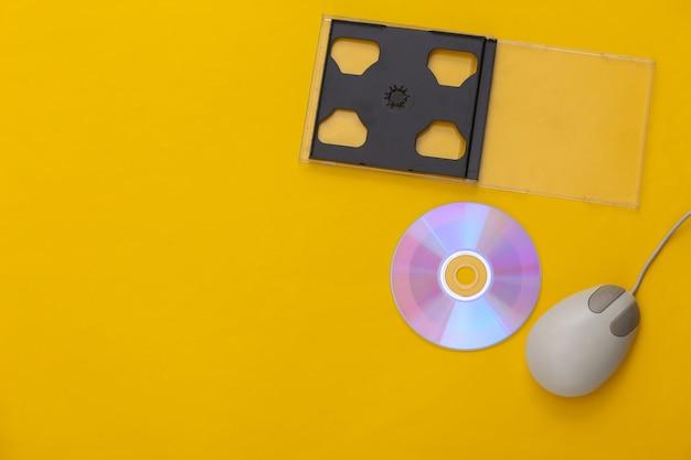 Ретро-электроника, компьютерная техника 90-х годов. компьютерная мышь, cd на желтом фоне. вид сверху