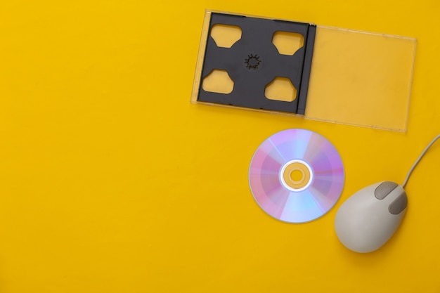 Retro electronics, pc technology 90s. pc mouse, cd on yellow background. top view