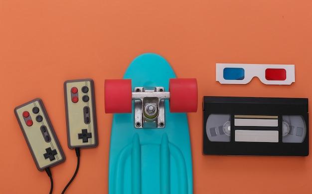 레트로 엔터테인먼트, 가제트 및 장치. 게임 패드, 크루저 보드, 비디오 카세트, 주황색 배경의 3d 안경. 80년대. 평면도. 플랫 레이