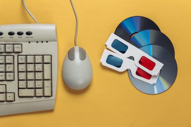 レトロなエンターテイメント。昔ながらのキーボード、pc マウス、コンパクト ディスク、黄色のアナグリフ ステレオ グラス