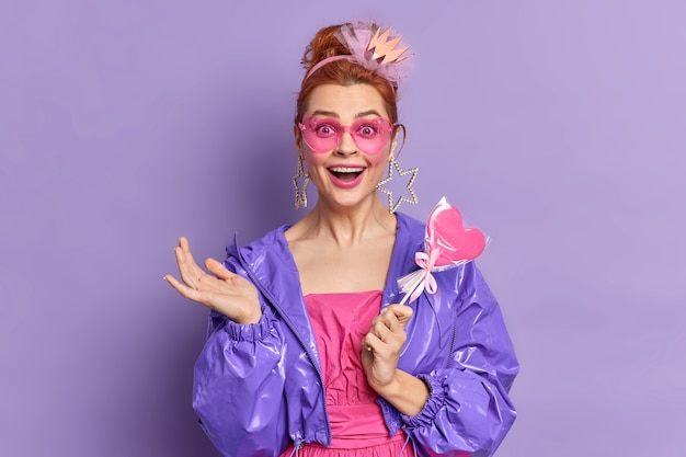 Ретро-фотомодель, одетая в стиле девяностых, имеет счастливое выражение, ностальгия держит позы восхитительных конфет на ярком фиолетовом фоне. модные тенденции. рыжая девушка в модных солнцезащитных очках фиолетовый пиджак