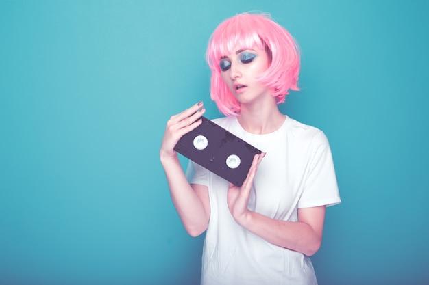 Концепция ретро моды. женщина с розовыми волосами, держащая пленку, изолированную в ярко-синей студии.