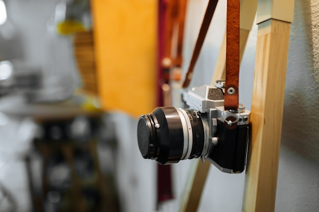 Retro film camera hangs on a strap against a white wall and a yellow warm lamp