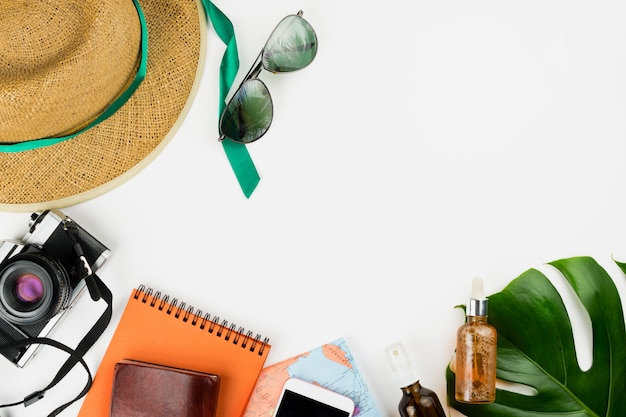 Retro film camera, map, notebooks, smartphone with black screen, cosmetics, straw hat and monstera leaves
