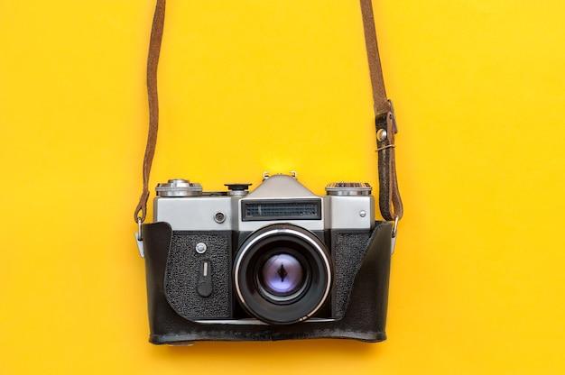 黄色の背景にレトロなフィルムカメラ